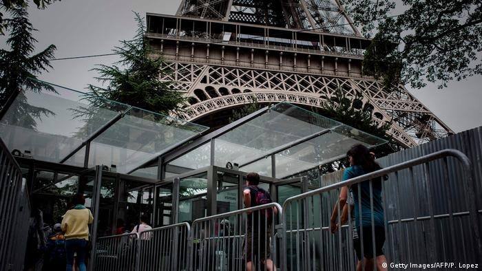 Tourists pass through a security barrier en route to the Eiffel tower.