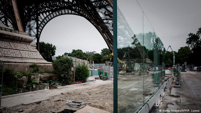 Bulletproof glass barrier goes up along one side of the Eiffel Tower.