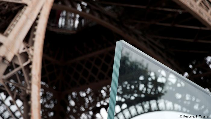 Close-up of a corner of the bulletproof glass against a backdrop of the lower tier of the Eiffel Tower.