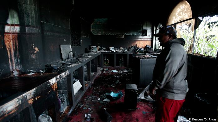 A man inspecting a house that was burned down by alleged paramilitary officers loyal to Nicaraguan President Daniel Ortega.