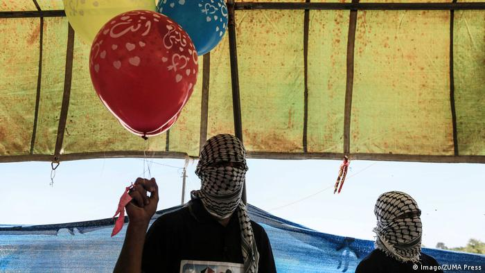 Palestinian protesters hold flammable balloon kites