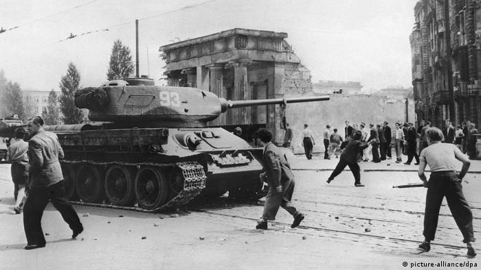 Historische schwarz-weiß Aufnahme vom 17. Juni 1953: Junge Männer bewerfen auf einer Straße mit Kopfsteinpflaster vor einer noch nicht wiederaufgebauten Kriegsruine einen sowjetischen Panzer mit Steinen