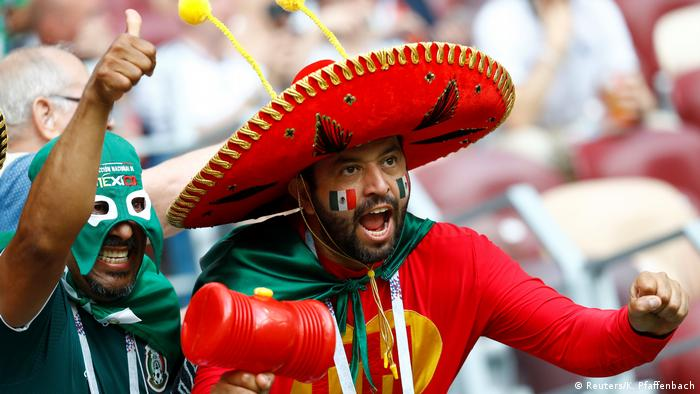 Two Mexico fans, dressed in colorful costumes (Reuters/K. Pfaffenbach)