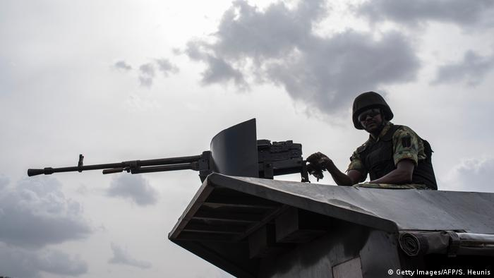 A Nigerian soldier mans the gun atop an armored vehicle during military exercises.