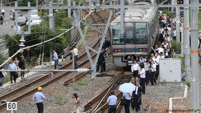 Passengers walk alongside tracks after the earthquake in Osaka