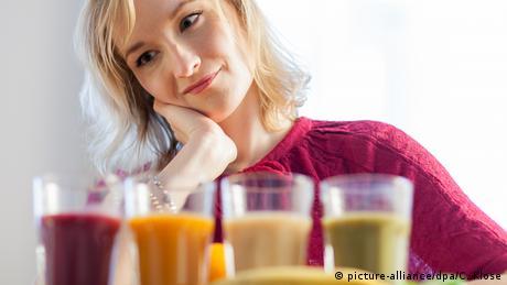 صورة تعبيرية لشابة تختار بين مشروبات طبيعية