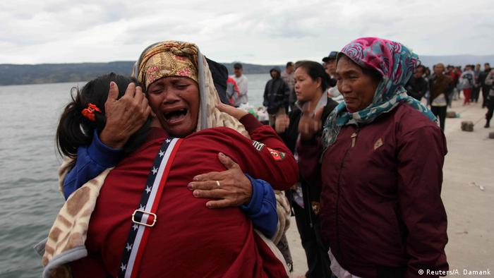 Relatives of missing people cry following a ferry accident in Indonesia (Reuters/A. Damank)