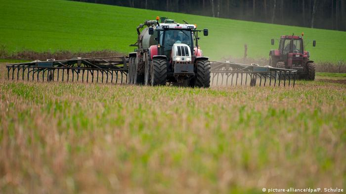 Un tractor rociando un campo con fertilizante.