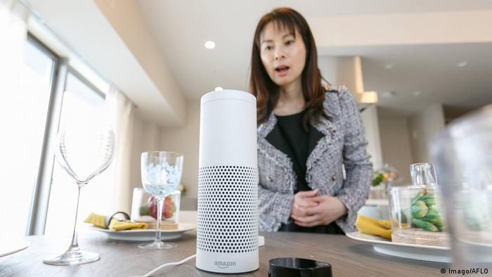 A woman talking to an Amazon Echo Plus