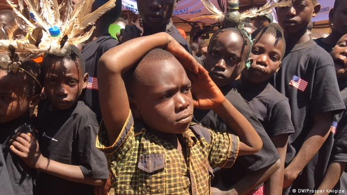 A young boy with hands over his head looked on by many kids