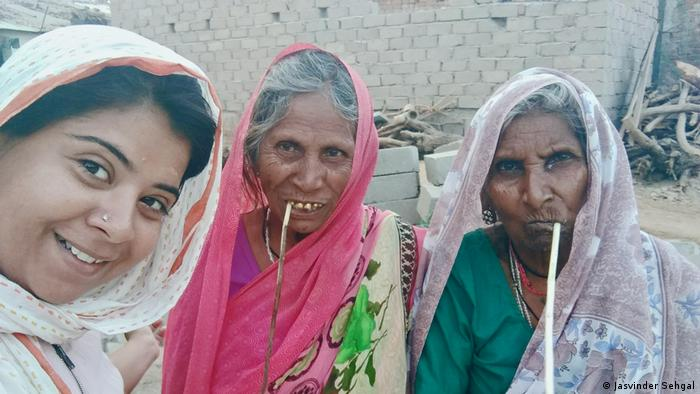 Two elderly ladies with sticks in their mouths, next to Rajeshwari Singh (Jasvinder Sehgal)