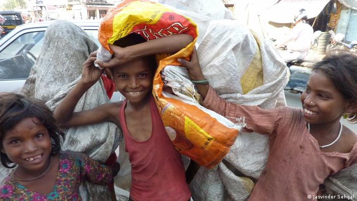 Niños recolectores de desperdicios sosteniendo un saco.