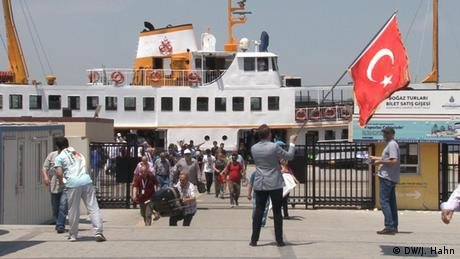 Emin Sarıoğlu waves a turkish flag as a people disembark on a pier from a ferry (DW/J. Hahn)