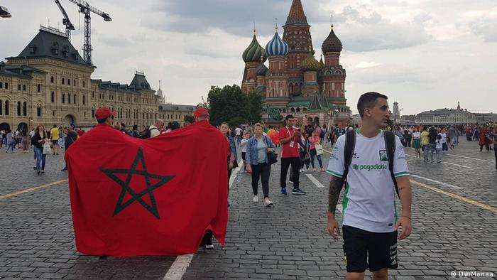 Two Moroccan fans carry their national flag draped on their shoulders on Red Square