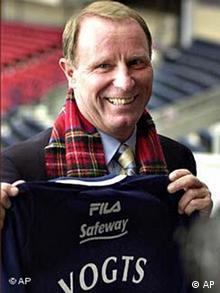 Berti Vogts holding up a Scotland jersey