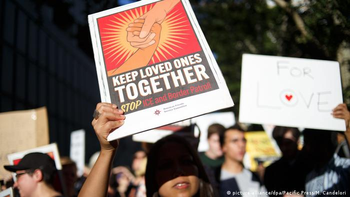 Protester holds sign that says: Keep loved ones together