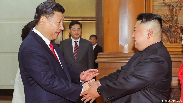 Chinese President Xi Jinping shakes hands with North Korean leader Kim Jong Un in Beijing