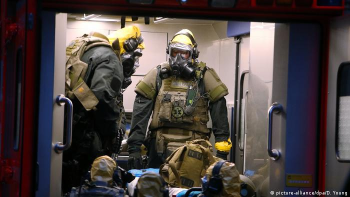 German authorities wearing protective clothing (picture-alliance/dpa/D. Young)