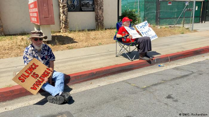 Two protesters sitting on a sidewalk in San Diego (DW/C. Richardson)