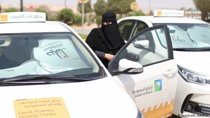 A fully veiled woman gets into a driving school car