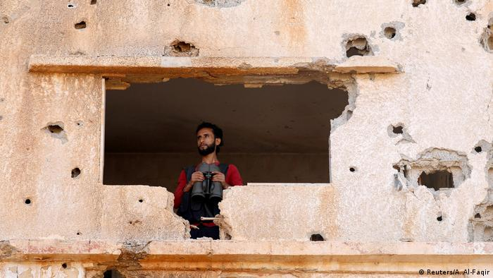 A fighter holding binoculars looks out of a damaged building