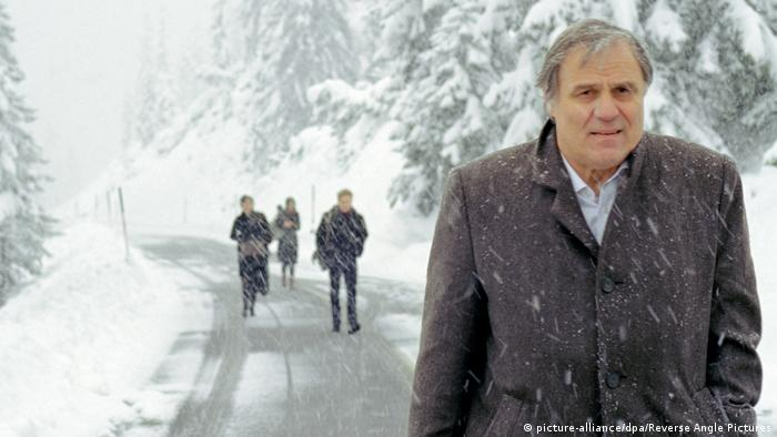 Still from the Architect, Josef Bierbichler walking in snowy mountain with three other people in background (picture-alliance/dpa/Reverse Angle Pictures)