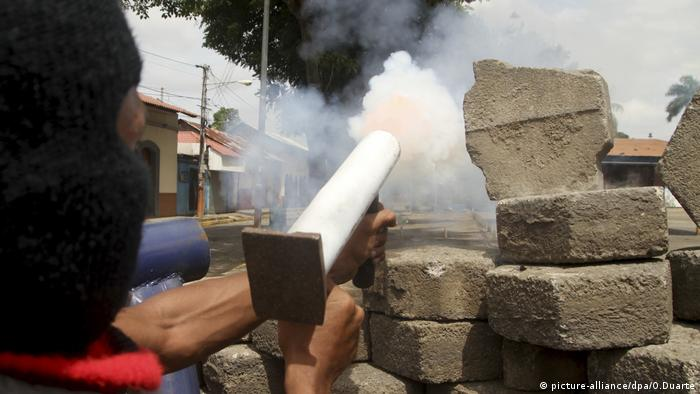 Protesters fire back at government forces behind a barricade
