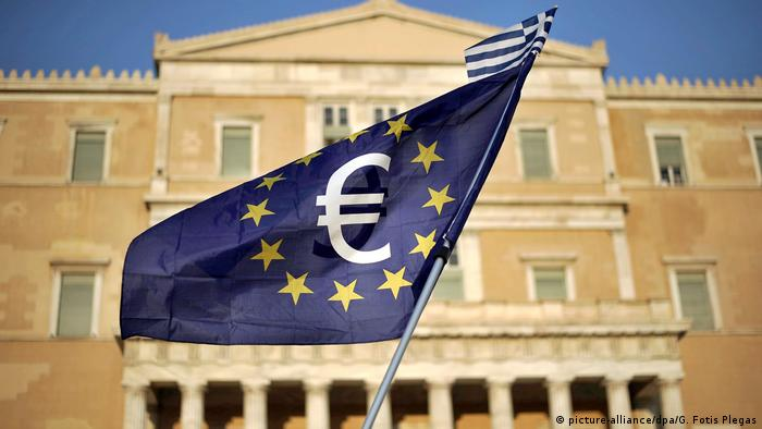 A European flag with the euro symbol in the middle of it in front of a building in Athens