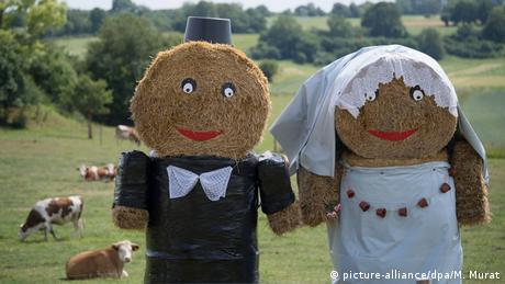 Strohballen, die als Brautpaar gestaltet wurden, stehen auf einer Kuhweide. (picture-alliance/dpa/M. Murat)