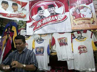 A man cleans his glasses near a shop selling election campaign t-shirts bearing portraits of Indonesian presidential candidates at a market in Jakarta, Indonesia, Wednesday, June 24, 2009. Indonesia will hold its presidential election on July 8. (AP Photo/Tatan Syuflana)