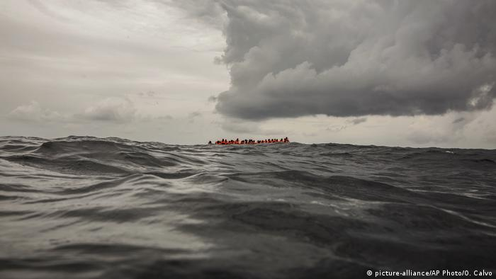 Migrants in the Mediterranean wait to be saved by a European rescue boat.
