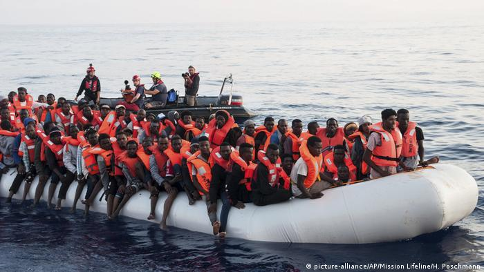 Migrants sit packed on a rubber boat in water