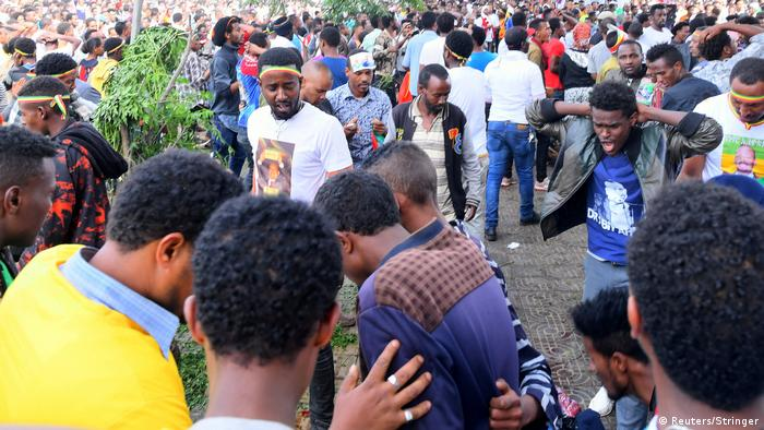 People react after a blast at a rally in Addis Ababa