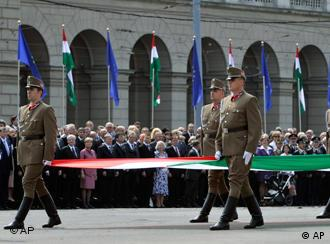 Hungarian guard of honor march with the nation's flag in front of foreign guests during a memorial day marking the 20th anniversary of the opening of the Iron Curtain in Budapest, Hungary, Saturday, June 27, 2009.