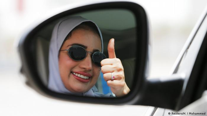 Woman giving thumbs-up in rear-vision mirror (Reuters/H. I Mohammed)