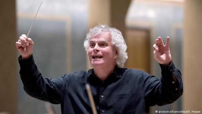 Sir Simon Rattle beaming while conducting (picture-alliance/dpa/S. Hoppe)