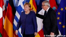 German Chancellor Angela Merkel is welcomed by European Commission President Jean-Claude Juncker at the start of an EU mini-summit on immigration in Brussels.