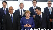 German Chancellor Angela Merkel, center, speaks with Spanish Prime Minister Pedro Sanchez, right, as they pose for a group photo at an informal EU summit on migration at EU headquarters in Brussels, Sunday, June 24, 2018. (Yves Herman, Pool Photo via AP) |