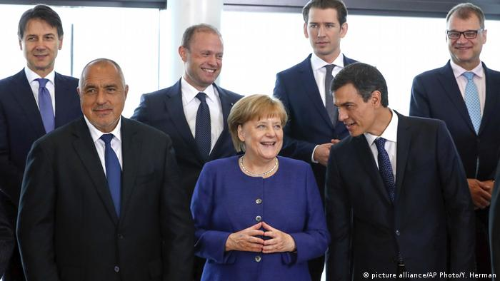 Merkel holds her hands together while surronded by other EU leaders