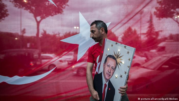 A man carries a picture of Turkish President Recep Tayyip Erdogan in front of a Turkish flag (picture-alliance/dpa/O.Weiken)