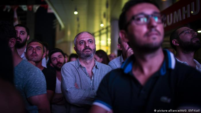 Men watch with stern expressions as the Turkish election results come in