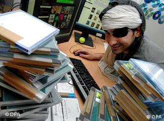 A man dressed as a pirate with an eyepatch at a computer behind piles of DVD cases