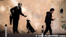 A man walks past a recent artwork by street artist Banksy in Paris on June 24, 2018. - Anonymous street artist Banksy's artwork of a man holding a handsaw behind his back and offering a bone to a dog which leg has been cut off, has been found near the Sorbonne University, in the center of Paris over the weekend. (Photo by Philippe LOPEZ / AFP) / RESTRICTED TO EDITORIAL USE - MANDATORY MENTION OF THE ARTIST UPON PUBLICATION - TO ILLUSTRATE THE EVENT AS SPECIFIED IN THE CAPTION (Photo credit should read PHILIPPE LOPEZ/AFP/Getty Images)