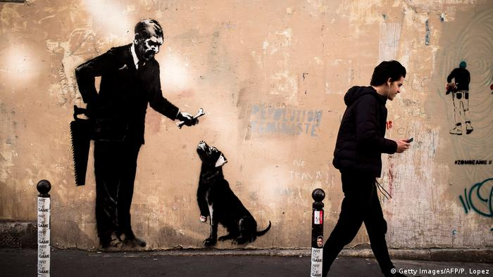 A Banksy mural: a man holding a handsaw behind his back and offering a bone to a dog which leg has been cut off, (Photo by Philippe LOPEZ / AFP)