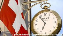 Schweizer Flagge neben Rolex Uhr
