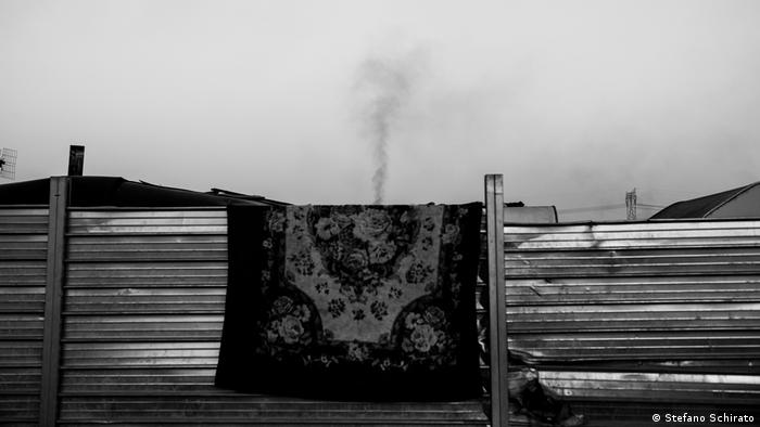 A rug hanging over a fence with smoke rising above it (Stefano Schirato)