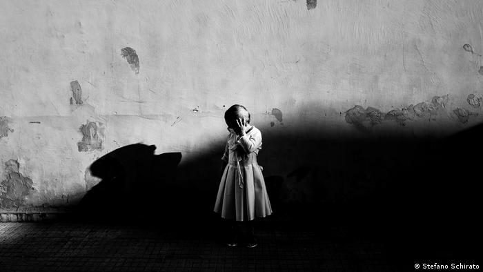 A young girl with a mask over her face (Stefano Schirato)