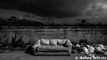 Black sky above landfill with a sofa in the middle. +++Dark skies over Campania: The Amalfi coast or the Pompeii ruins are just a few of the many attractions Campania has to offer. But while the picturesque Italian region gave birth to pizza, it's also home to the Triangle of Death, an area between the cities of Naples and Caserta where people are forced to live amid garbage, breathe toxic fumes from burning landfills and drink poisoned water due to illegally disposed waste. Foto: Stefano Schirato, 2015-2018, Italy