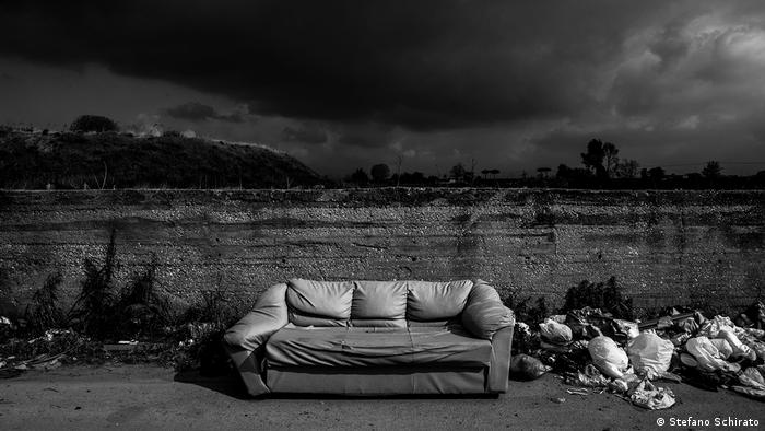 Black sky above landfill with a sofa in the middle (Stefano Schirato)