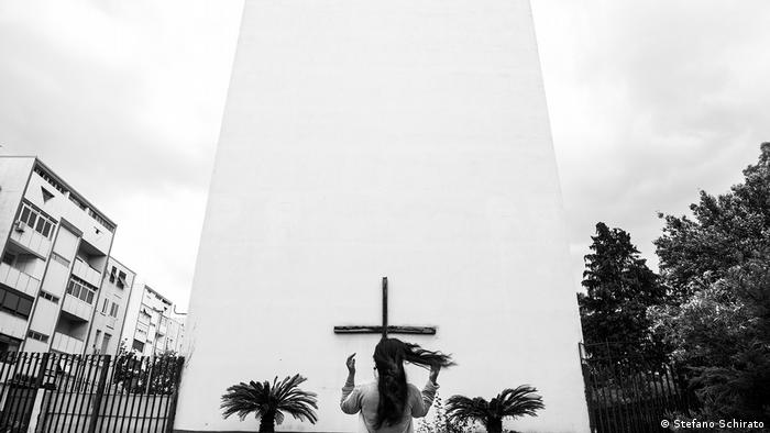 A woman standing in front of a cross on a white wall (Stefano Schirato)